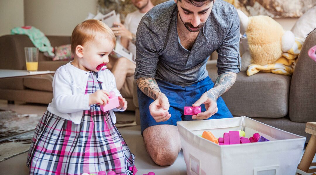 Same sex couple at home playing blocks with baby girl.