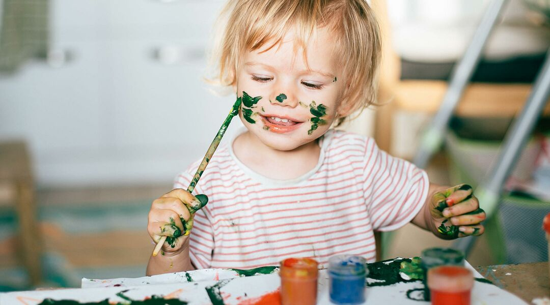 Child painting his own face in green