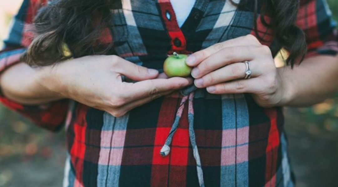Woman in flannel shirt holding tiny apple above her baby bump