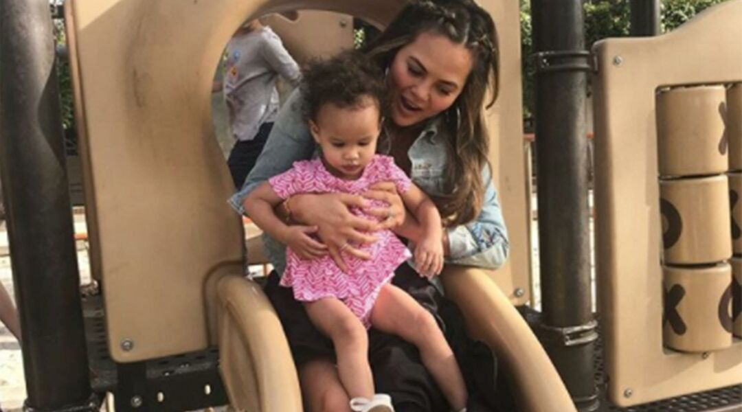 Chrissy Teigen going down a playground slide with Luna