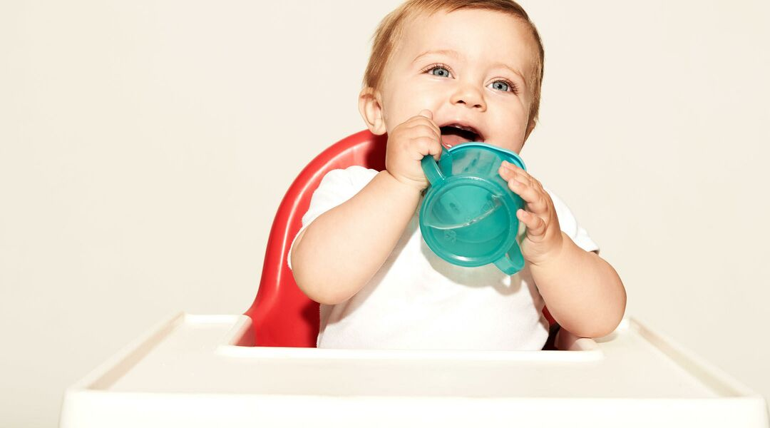Happy baby holding sippy cup in high chair.