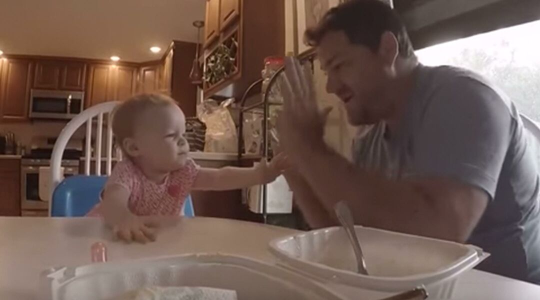 Dad and baby doing sign language at the kitchen table