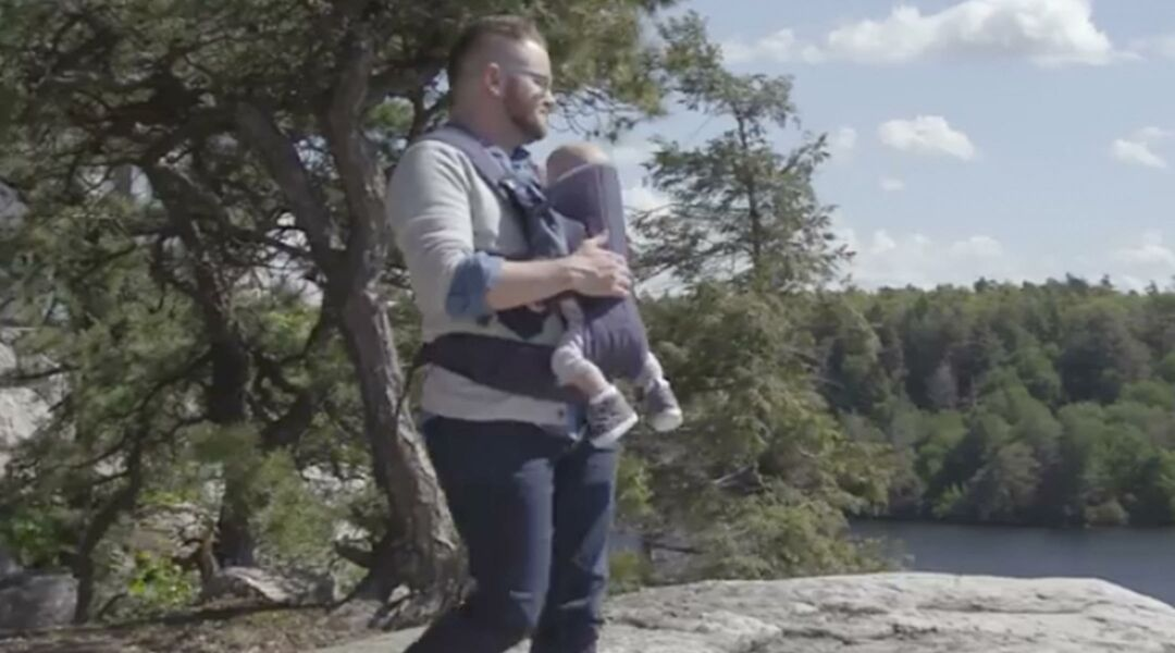 Dad outdoors with son in infant carrier