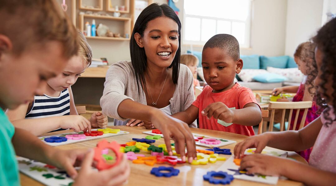Day care employee playing with kids at table