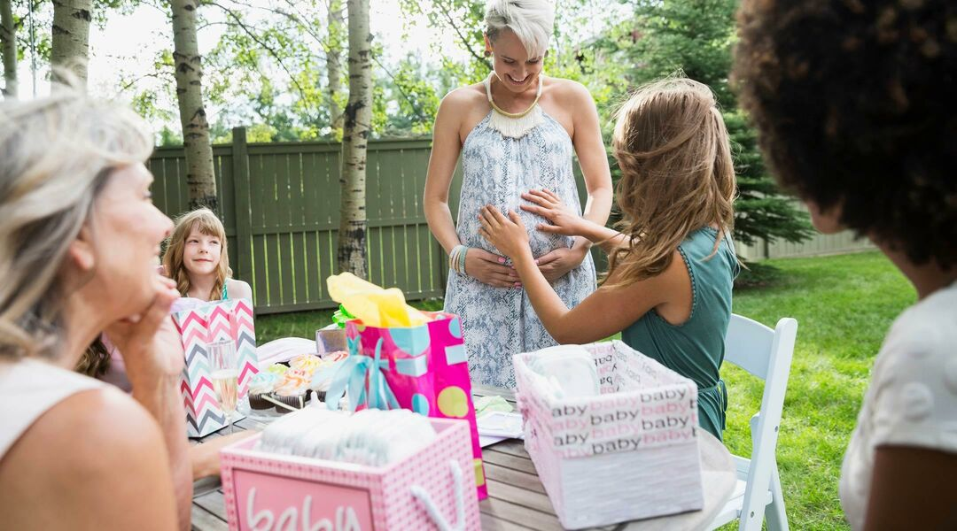 Pregnant woman at her baby shower in backyard surrounding by friends and family.