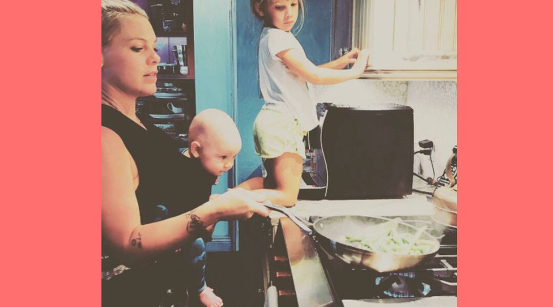 Pink cooking while babywearing her son