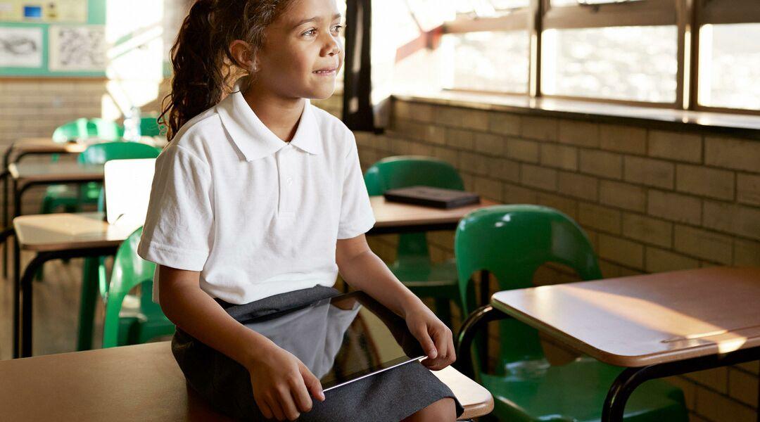 smart little girl smiling in empty classroom
