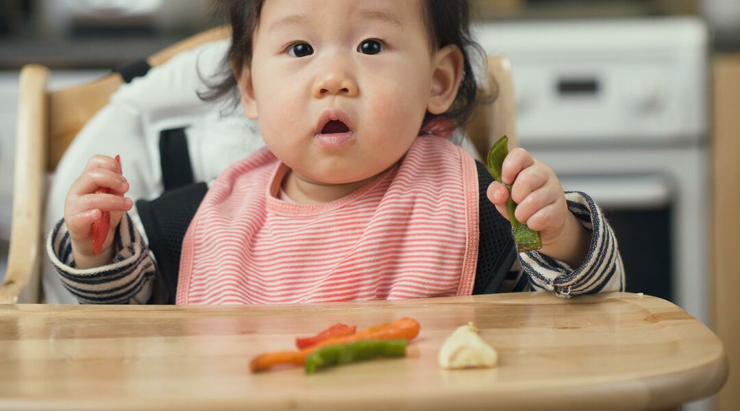 Baby playing with vegetables in high chair