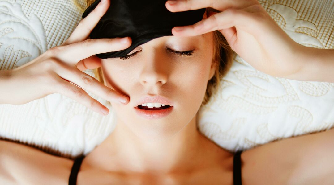 Tired woman in bed waking up and removing eye mask.