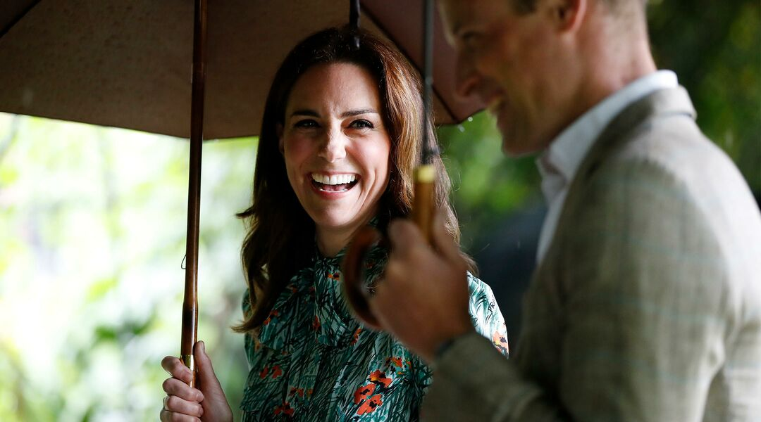 Kate Middleton laughing while standing under an umbrella next to Prince William
