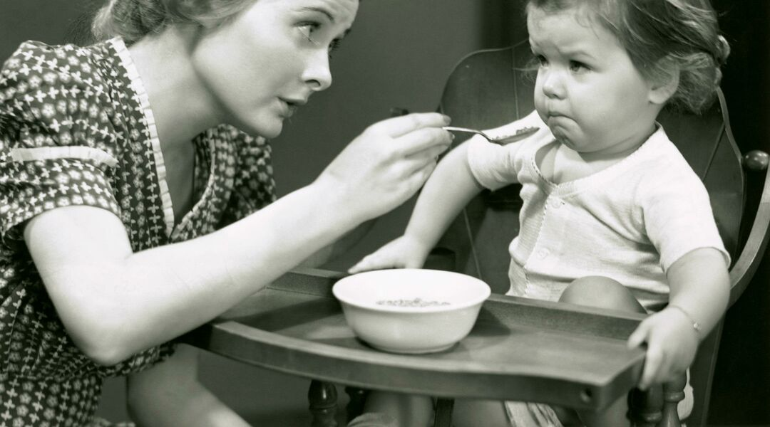 retro image of mom trying to feed toddler who is refusing food