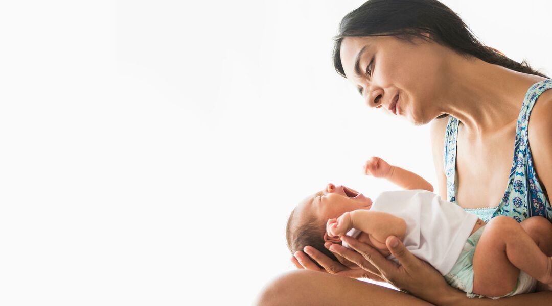 Mom singing to newborn baby