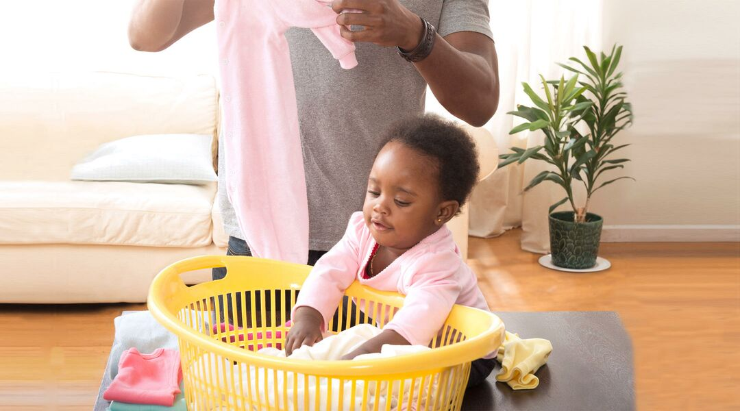 dad folding basket of laundry clothes with baby daughter
