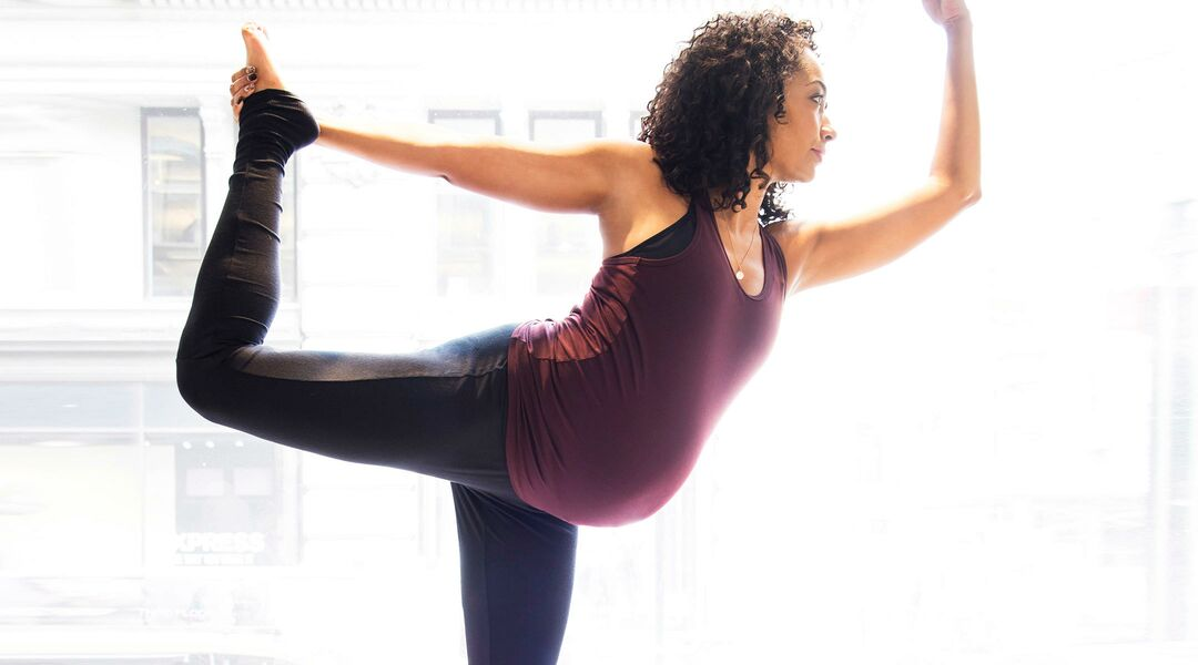 pregnant woman wearing fitness clothes and doing yoga