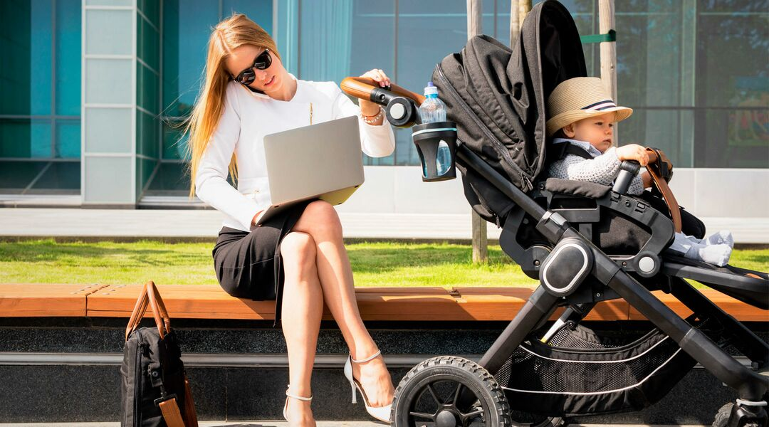 woman sitting on bench with laptop next to a baby in a stroller