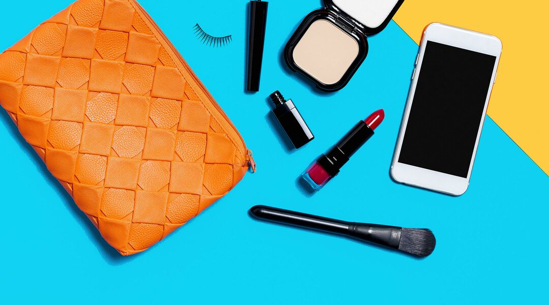 make-up bag flat lay beauty products