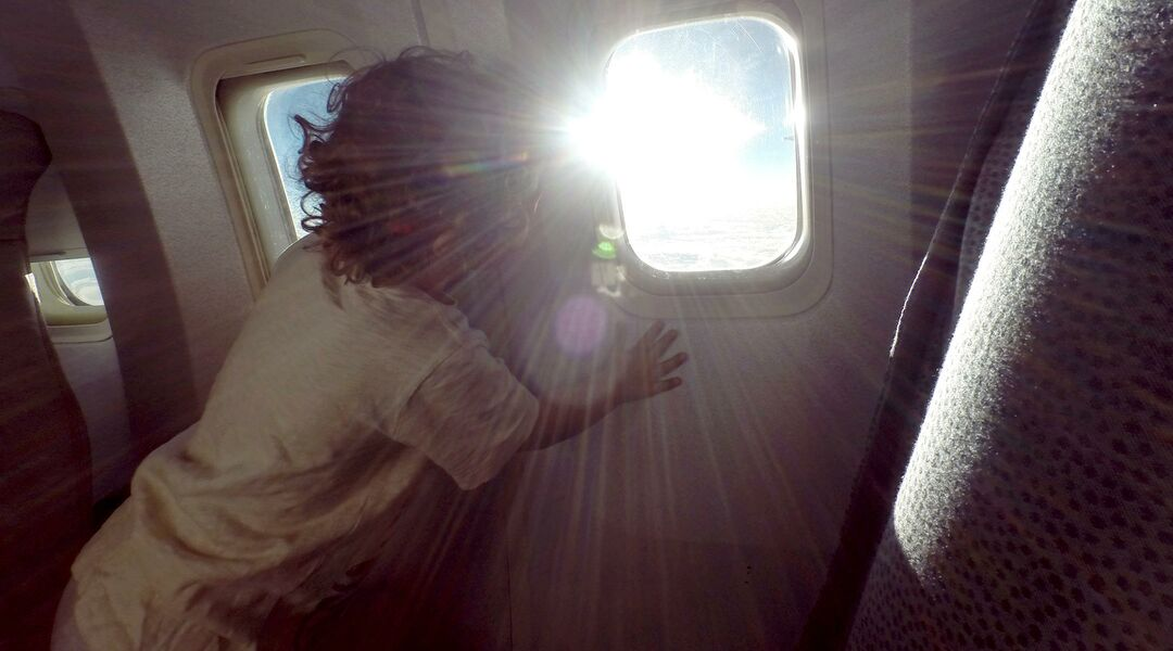 Toddler looking out sunny airplane window