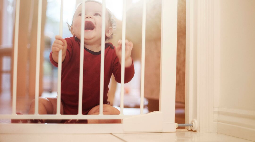 A baby holds the bars of a child-proofing gate, one of the measures that parents take to protect their children.