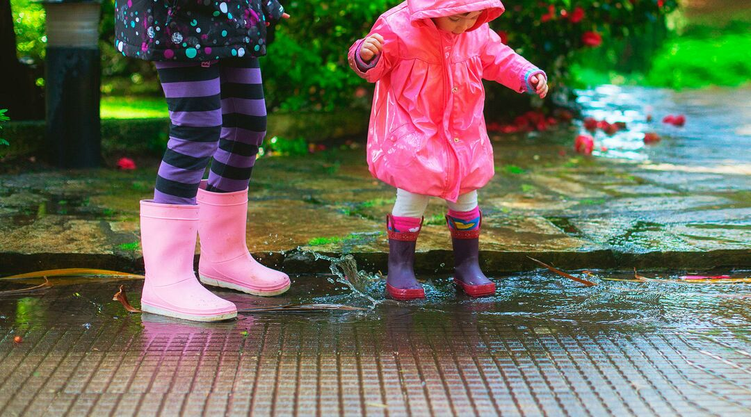 toddler playing in the rain wearing rain boots