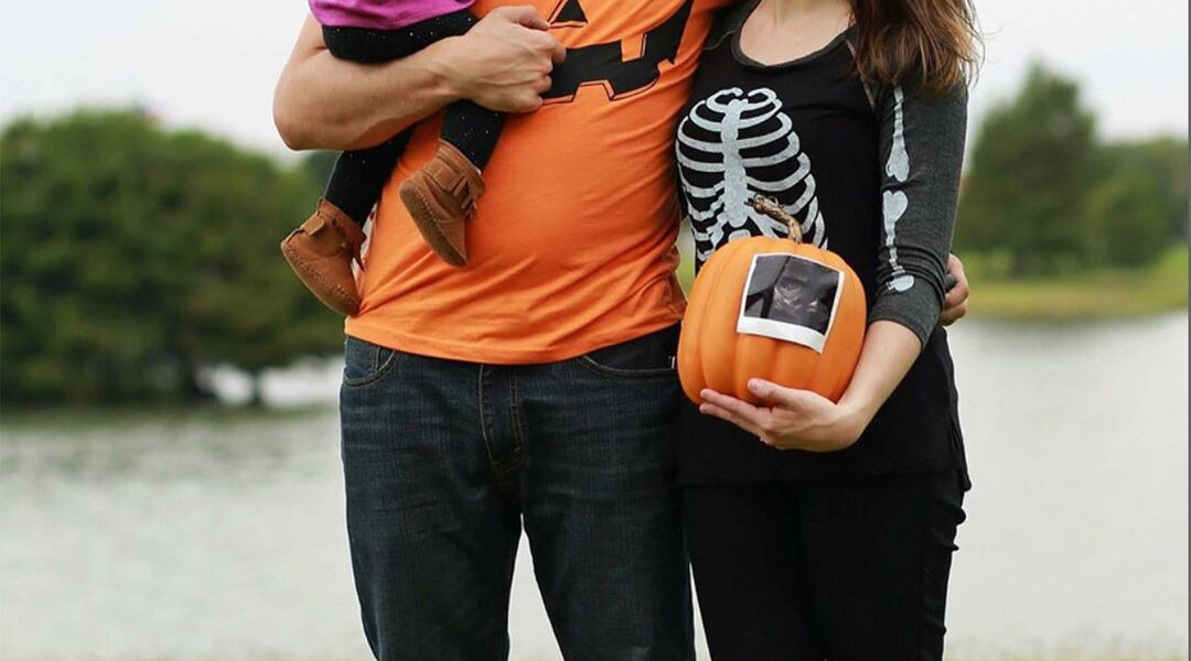 Family in Halloween shirts with sonogram pumpkin