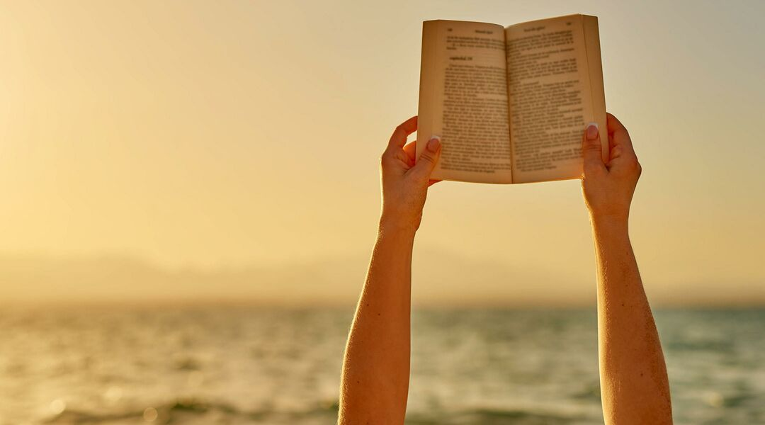 hands holding book up at beach
