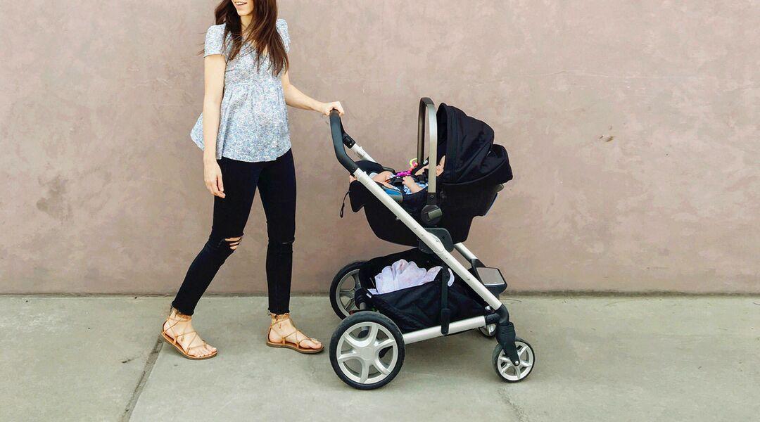 Mom walking baby in stroller against beige wall.