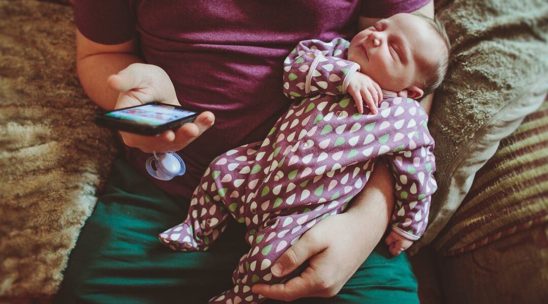Parent checking phone while holding baby