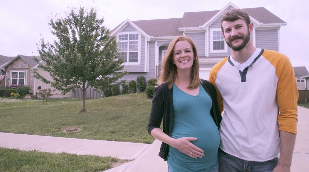 pregnant wife and husband standing in front of house