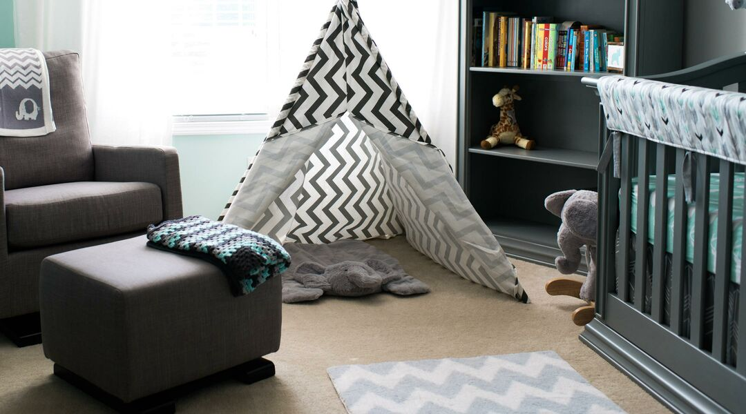 Baby nursery focused on fun tee-pee and book shelf.