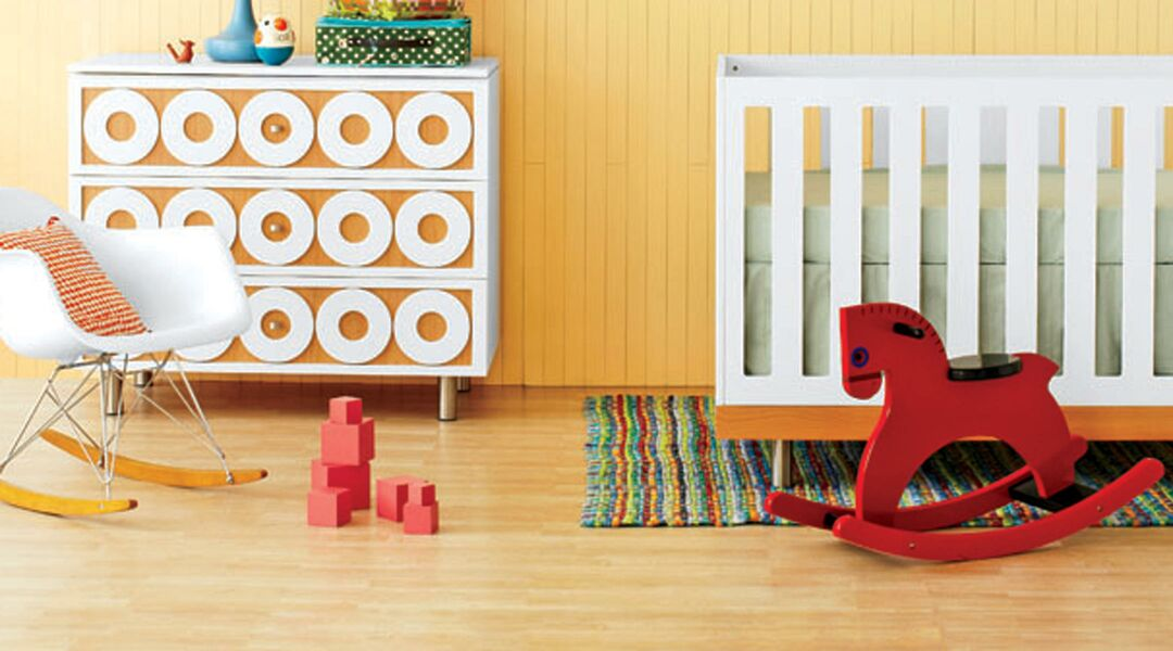 Gender neutral baby nursery containing crib and red rocking horse.