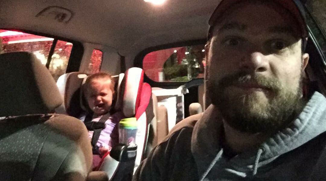 Dad taking a selfie in a car while his daughter has a tantrum in her car seat