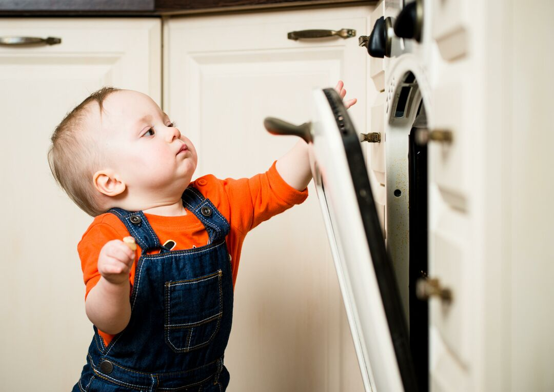 Baby trying to open oven