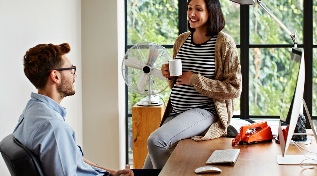 pregnant woman talking to partner at home