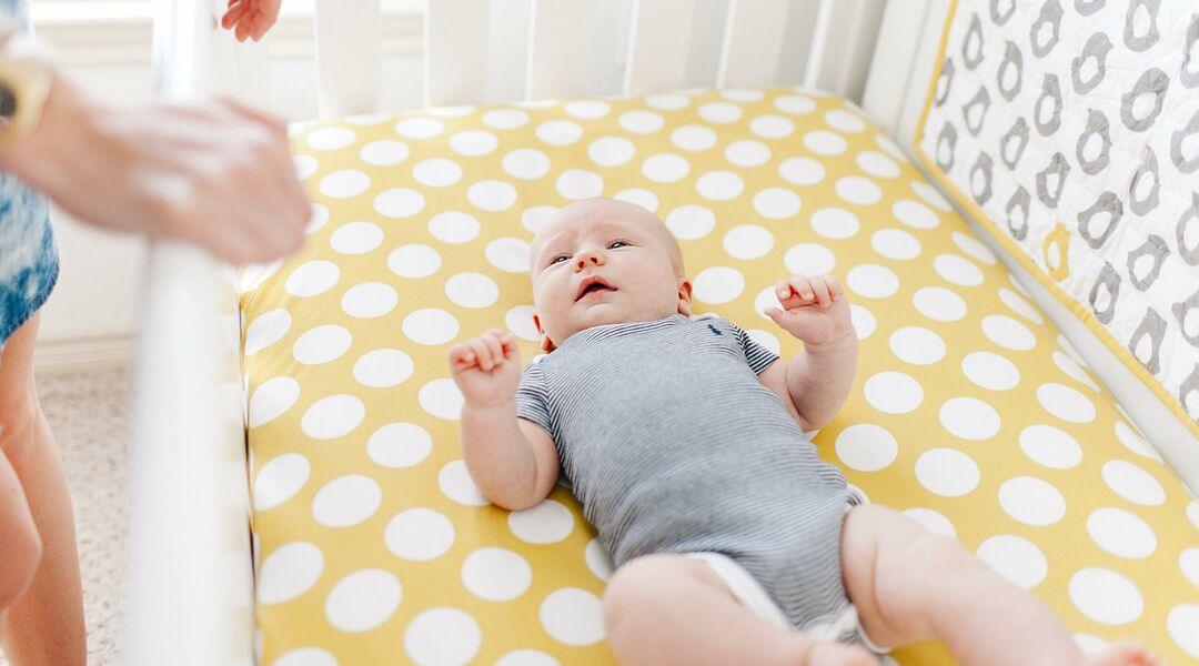 parent putting baby to sleep in crib being mindful of sids
