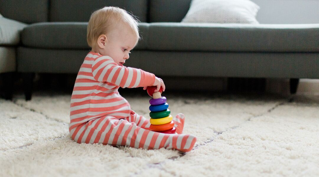 Baby in pajamas playing with ring toy