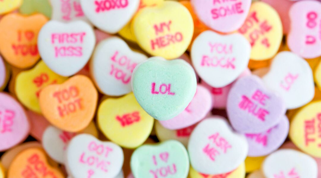 Pile of candy hearts with messaging, center one reading LOL.