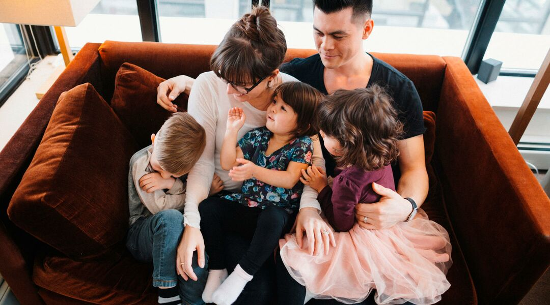 family with three kids hanging out on couch.