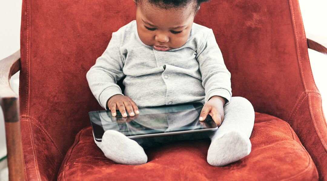 A baby sits on a chair and plays with a tablet