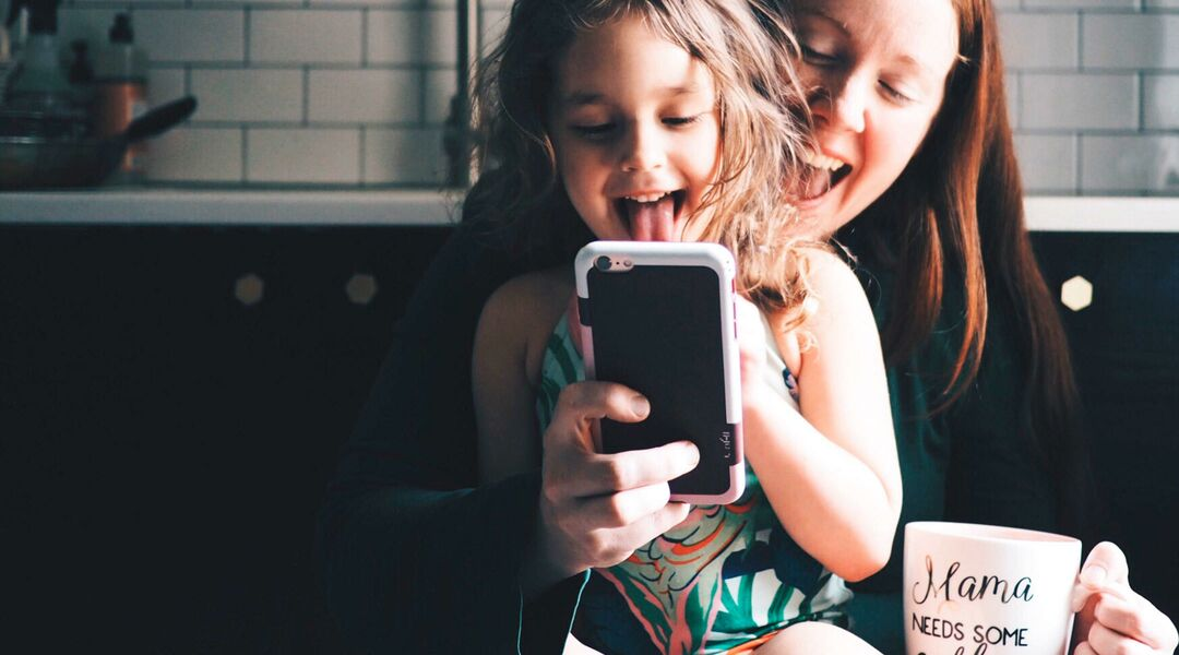 mom and toddler daughter at home, viewing video on phone