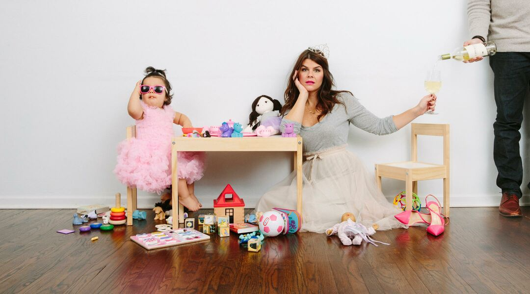 Leslie Bruce slumps at a kid's table, surrounded by toys, wearing an off-kilter tiara and holding her glass up while a man pours her some wine.