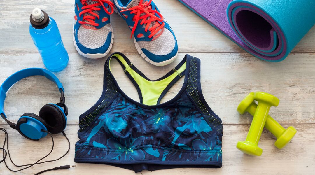 Arrangement of exercise gear, a water bottle, sports bra, shoes and free weights.