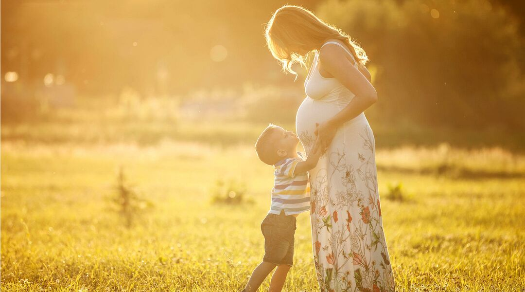 Pregnant mother in summer maternity clothes with a child