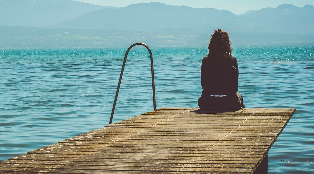 sad woman sitting on dock surrounded by beautiful lake and mountain landscape