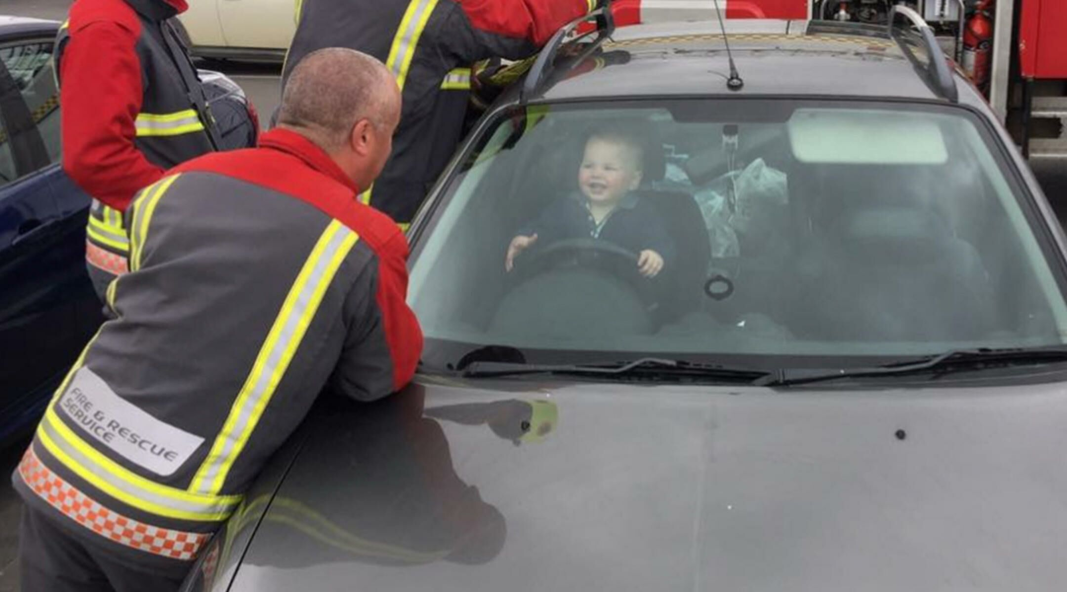 Firefighters Rescuing A Grinning Toddler Boy From Car