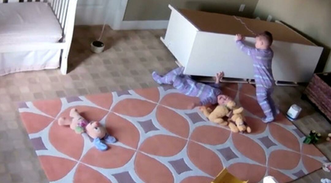 Toddler lifting dresser off his pinned twin brother