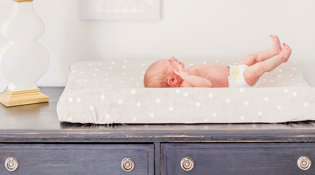 newborn baby in nursery on changing table