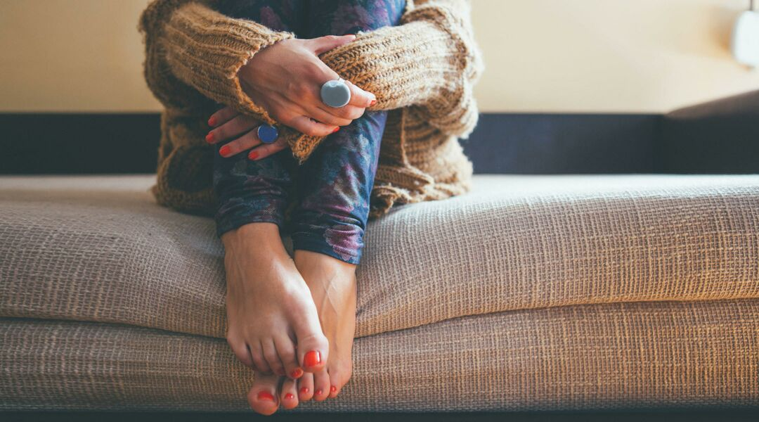 A woman's arms wrap protectively around her legs as she sits on a couch.