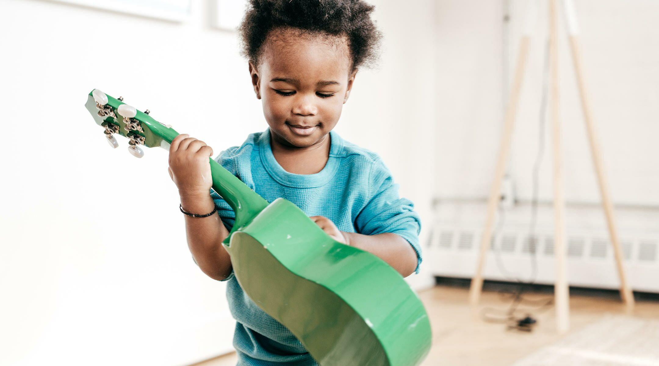 toddler playing green guitar