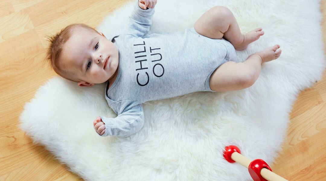 Baby wearing onesie that says chill out.