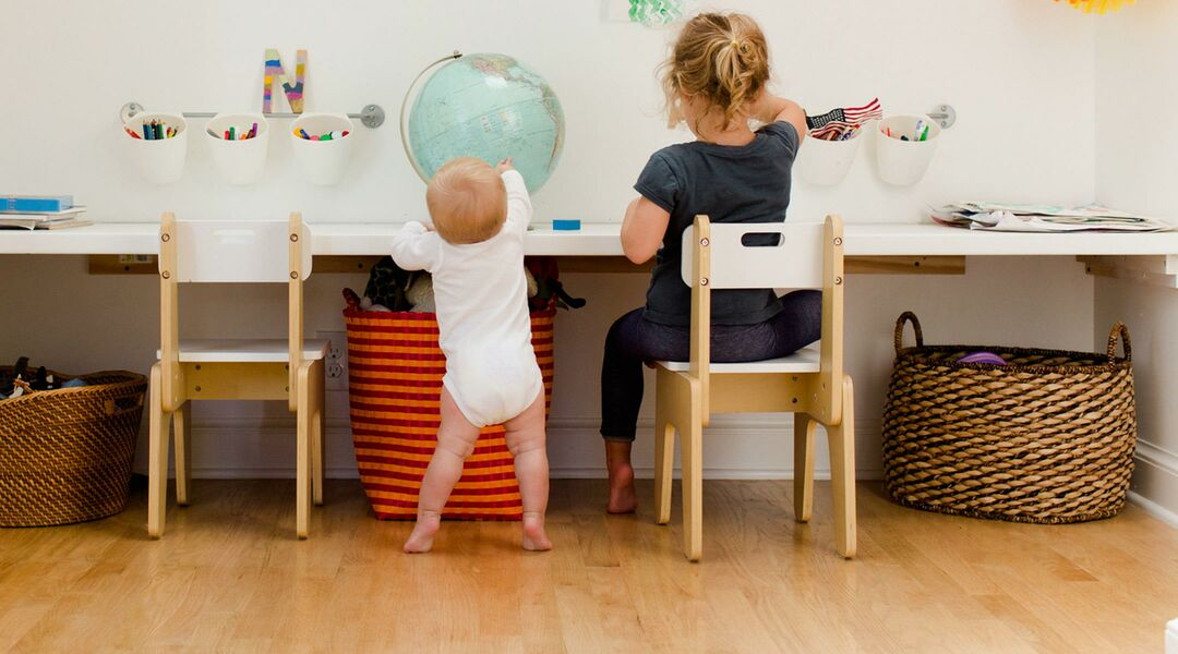 toddler standing next to young child seated at desk